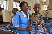 Nurse Christine Happy sits with a young patient at Bwindi Community Hospital. 4-year-old Junior had surgery to remove an abyss from his chest and is now recovering in the children's ward. Standards of patient care and cleanliness at the hospital are extremely high. The Bwindi Community Hospital is in Buhoma Village on the edge of the Bwindi Impenetrable Forest in Western Uganda. It serves around 250,000 people from the surrounding area.