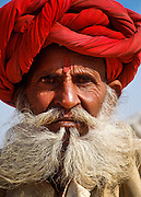 An elderly bearded Rajasthani man with a red turban during the Pushkar Cattle Fair in the deserts of Rajasthan India