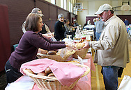 Theresa Fishleder (from left) of Cedar Rapids helps Mike Aubey of Cedar Rapids bag a loaf of bread at her booth, Theresa's Real Bread, during the Indoor Winter Farmers Market at the First Street Community Center at 221 First Street NE in Mount Vernon on Saturday, April 16, 2011.