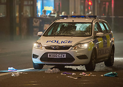 © Licensed to London News Pictures. 29/11/2014.  Bristol, UK. A shoe can be seen as a Police patrol car is examined by police after a collision with a woman in Stokes Croft which was closed to traffic on a busy Saturday night.  The woman suffered potentially life threatening head injuries after the patrol car was on an emergency response call to reports of a man with a knife making threats.  A man was arrested.  Photo credit : Simon Chapman/LNP