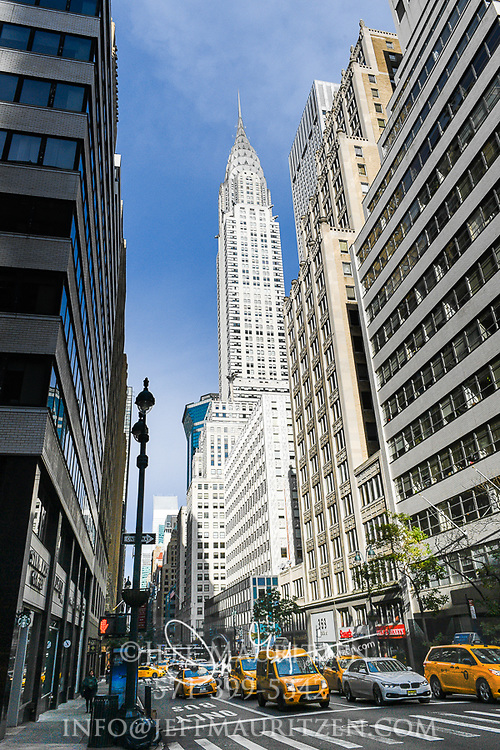 Yellow taxis and other cars drive beneath the Chrysler building in Manhattan, New York City.