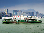 "10 AUGUST 2013 - HONG KONG:  Star Ferry ships cross Victoria Harbor. The Star Ferry, or The ""Star"" Ferry Company, is a passenger ferry service operator and tourist attraction in Hong Kong. Its principal routes carry passengers across Victoria Harbour, between Hong Kong Island and Kowloon. It was founded in 1888 as the Kowloon Ferry Company, adopting its present name in 1898.<br /> The fleet of twelve ferries currently operates two routes (four prior to April 1, 2011) across the harbour, carrying over 70,000 passengers a day, or 26 million a year. Even though the harbour is crossed by railway and road tunnels, the Star Ferry continues to provide an inexpensive mode of harbour crossing. The company's main route runs between Central and Tsim Sha Tsui. Hong Kong is one of the two Special Administrative Regions of the People's Republic of China, Macau is the other. It is situated on China's south coast and, enclosed by the Pearl River Delta and South China Sea, it is known for its skyline and deep natural harbour. Hong Kong is one of the most densely populated areas in the world, the  population is 93.6% ethnic Chinese and 6.4% from other groups. The Han Chinese majority originate mainly from the cities of Guangzhou and Taishan in the neighbouring Guangdong province.      PHOTO BY JACK KURTZ"