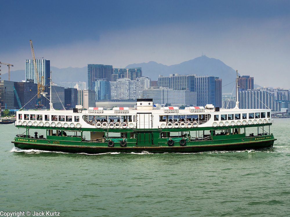 """10 AUGUST 2013 - HONG KONG:  Star Ferry ships cross Victoria Harbor. The Star Ferry, or The """"Star"""" Ferry Company, is a passenger ferry service operator and tourist attraction in Hong Kong. Its principal routes carry passengers across Victoria Harbour, between Hong Kong Island and Kowloon. It was founded in 1888 as the Kowloon Ferry Company, adopting its present name in 1898.<br /> The fleet of twelve ferries currently operates two routes (four prior to April 1, 2011) across the harbour, carrying over 70,000 passengers a day, or 26 million a year. Even though the harbour is crossed by railway and road tunnels, the Star Ferry continues to provide an inexpensive mode of harbour crossing. The company's main route runs between Central and Tsim Sha Tsui. Hong Kong is one of the two Special Administrative Regions of the People's Republic of China, Macau is the other. It is situated on China's south coast and, enclosed by the Pearl River Delta and South China Sea, it is known for its skyline and deep natural harbour. Hong Kong is one of the most densely populated areas in the world, the  population is 93.6% ethnic Chinese and 6.4% from other groups. The Han Chinese majority originate mainly from the cities of Guangzhou and Taishan in the neighbouring Guangdong province.      PHOTO BY JACK KURTZ"""