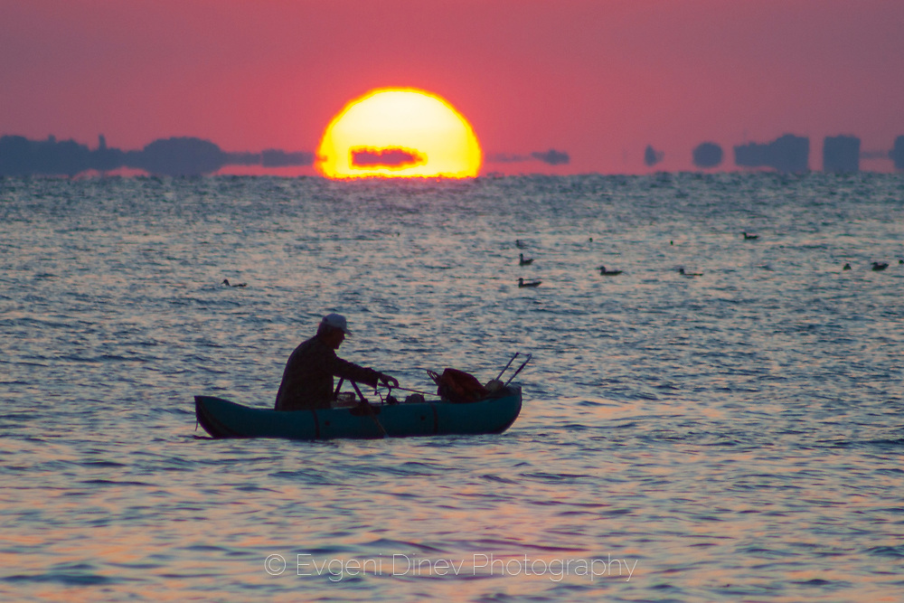 Fisherman at the sea at sunrise