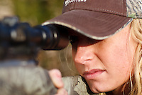 female deer hunter looking through a scope while deer hunting with a muzzloader
