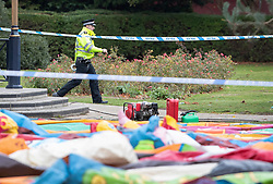 © Licensed to London News Pictures. 04/11/2018. Woking, UK. A police officer walks round a cordon surrounding a deflated slide in Woking Park after it collapsed injuring eight children. The park was holding a fireworks party when the accident happened. Photo credit: Peter Macdiarmid/LNP