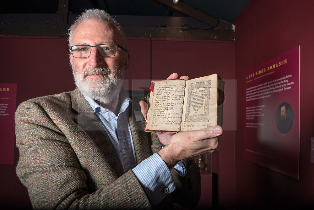 © Licensed to London News Pictures. 16/04/2018. Winchcombe, Gloucestershire, UK. Sudeley Castle's 'Royal Sudeley 1,000, Trials, Triumphs and Treasures'. Picture of DEREK MADDOCK, Sudeley Castle Archivist, holding a book with wife of Henry VIII Katherine Parr's formal signature. Treasures from Sudeley Castle's 1,000 year history have gone on show in a new exhibition. Called 'Royal Sudeley 1,000, Trials, Triumphs and Treasures', the newly refurbished exhibition includes a collection of priceless objects and curiosities. The exhibition includes a one-of-a-kind, life-size glass-engraved portrait of Katherine Parr by critically acclaimed artist, John Hutton. The artwork was re-discovered during the refurbishment of a holiday cottage on the estate, where it had been for decades. Its importance has now been realised and so it has been brought into the exhibition collection. Numerous items of historic significance are also on display, such as a lock of Katherine Parr's hair, her prayer book and an intricate lace christening canopy believed to have been worked on by Anne Boleyn for the christening of her daughter, Elizabeth I. Sudeley was a royal residence, closely associated with some of the most famous English monarchs, including Edward IV, Richard III, Henry VIII, Lady Jane Grey, Katherine Parr, Elizabeth I and Charles I. The Castle was even home to a secret Queen of England, Eleanor Boteler, whose royal status was unknown for centuries. Photo credit: Simon Chapman/LNP