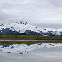 Mt. Douglas reflects in the tidal pool near the beach. Katmai National Park, Alaska