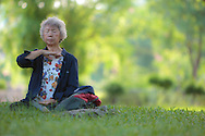 A woman meditates in the early morning at Lumpini Park, Bangkok, Thailand
