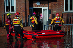 © Licensed to London News Pictures. 27/12/2015. York, UK.  Member of a mountain rescue team talk to a family on their doorstep asking if they want to be evacuated. . Large areas of the North of England have been hit by severe flooding following unusually heavy rainfall in December. Photo credit: Ben Cawthra/LNP
