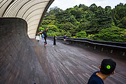 A group of Singaporean youths spend their weekend skateboarding on Henderson Waves bridge, Singapore's highest pedestrian bridge built 36 meters above the road. <br /> What does the future of cities look like? I explore Singapore and its continuous vertical development as it tries to balance the urban cityscape of sky scrapers with artificial nature by installing vast green walls. Photo by Suzanne Lee/Panos Pictures