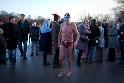 © Licensed to London News Pictures. 25/12/2013. London, UK. A members of the Serpentine Swimming Club walks back to the changing rooms after completing the Serpentine Swimming Club's annual Christmas morning 'Peter Pan Cup' race in Hyde Park, London, today (25/12/2013). The race, which takes place every Christmas Day on the Serpentine River, takes its name from from the novel by J.M.Barrie after the author presented the first Peter Pan Cup in 1904. Photo credit: Matt Cetti-Roberts/LNP