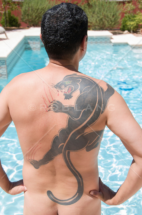 nude man with a large tattoo of a panther on his back outdoors by a swimming pool