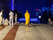 08 SEPTEMBER 2013 - BANGKOK, THAILAND: A monk walks over a bridge into the site of a mass alms giving service in Bangkok Sunday. 10,000 Buddhist monks participated in a mass alms giving ceremony on Rajadamri Road in front of Central World shopping mall in Bangkok. The alms giving was to benefit disaster victims in Thailand and assist Buddhist temples in the insurgency wracked southern provinces of Thailand.      PHOTO BY JACK KURTZ