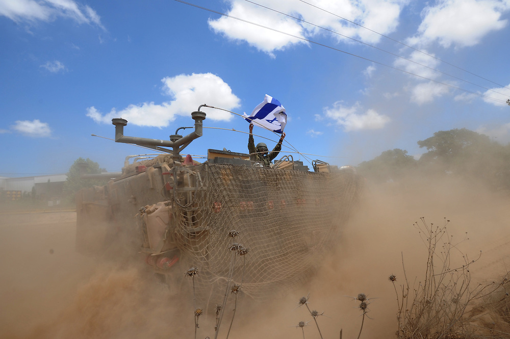 UNSPECIFIED, ISRAEL - JULY 18, 2014: An Israeli soldier waves an Israeli flag atop an APC on the move to an army deployment area near Israel's border with the Gaza Strip, on July 18, 2014.  Israel has launched a ground invasion into Gaza Strip, targeting terror tunnels. Photo by Gili Yaari