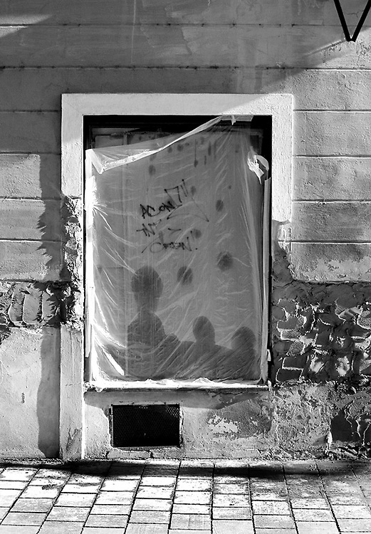 .Wet plastic sheeting over the window of a derelict building gives the impression of people. From Neighborhoods series
