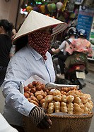 A Vietnamese woman wearing a conical hat selling pastries from a basket in the Old Quarter, Hanoi, Vietnam, Southeast Asia