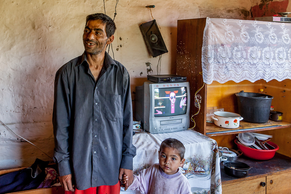 Portrait of grandfather Lubomir (42) with his son at the families house in the Roma settlement in Ostrovany.