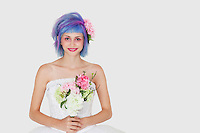 Portrait of happy young woman in wedding dress with dyed hair against gray background