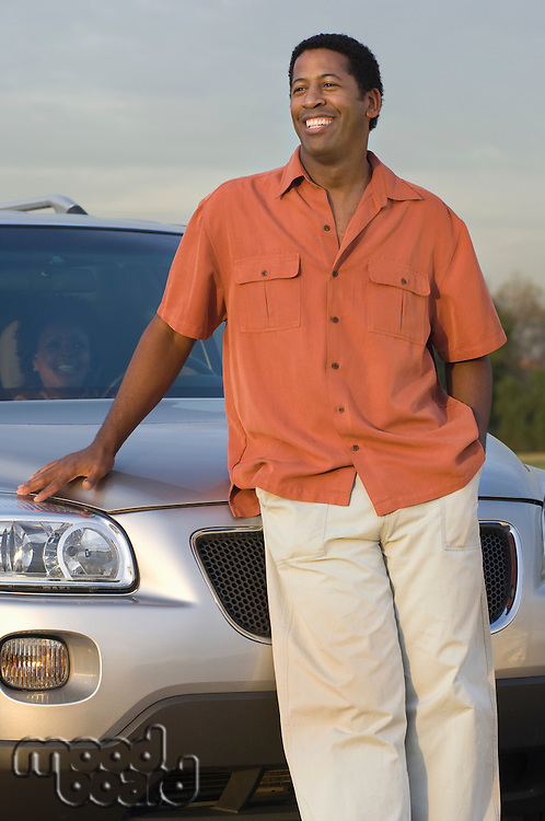 Mid adult man in front of car, smiling