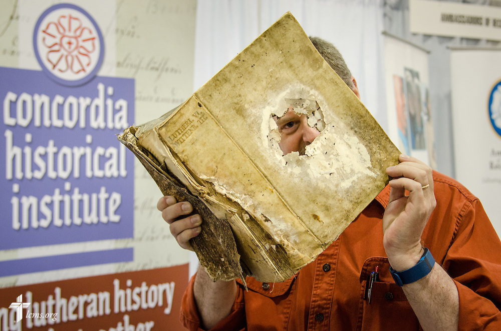 The Rev. Dr. Daniel Harmelink, executive director of Concordia Historical Institute, exhibits an original copy of Luther's Works Vol. VI published in 1553 in Wittenberg, Germany, on Friday, July 8, 2016, before the start of the 66th Regular Convention of The Lutheran Church–Missouri Synod at the Wisconsin Center in Milwaukee. LCMS Communications/Frank Kohn
