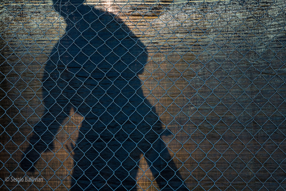 Workers are silhouetted behind a construction fence lined with privacy cloth.