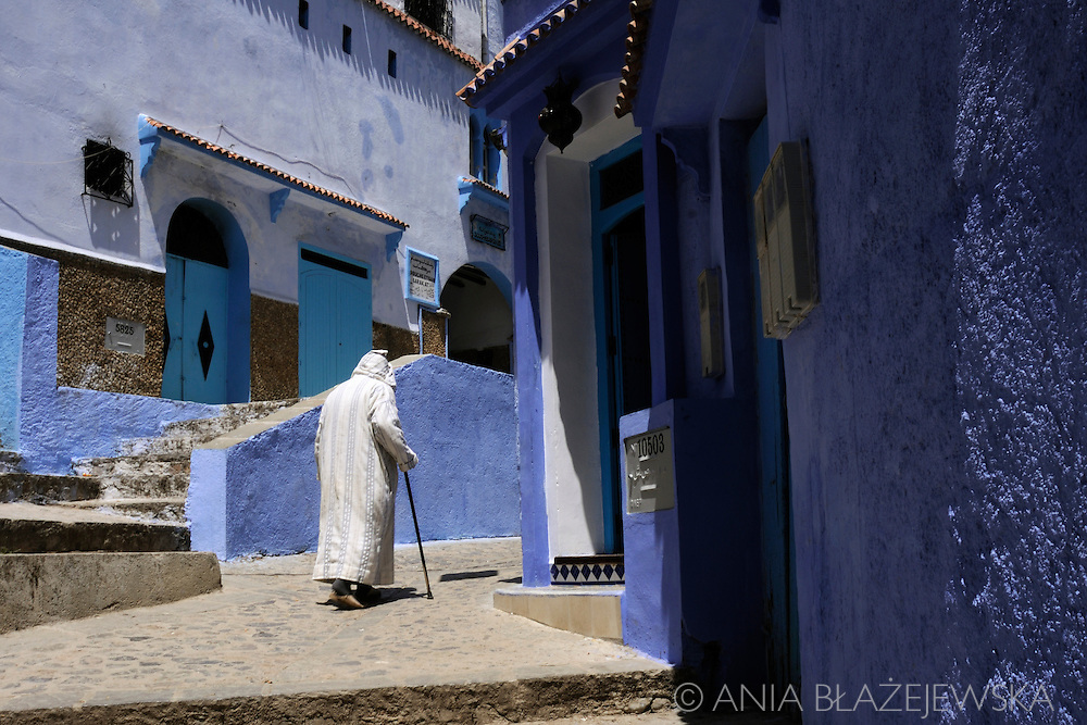 Morocco, Chefchaouen. Man in jellaba walking the street of the blue medina.