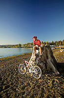 An old growth stump makes a nice perch for a mountain biker relaxing and enjoying the view of Georgia Strait, after a ride along the Oyster River.  Black Creek, Vancouver Island, British Columbia, Canada.