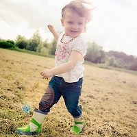 A girl playing in a field with lensflare