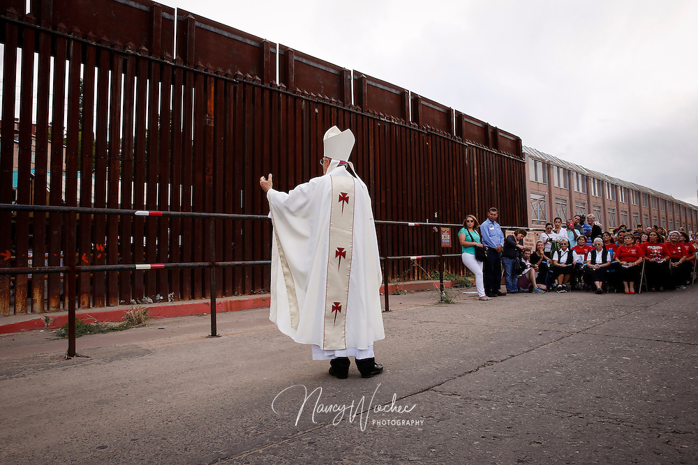 Bishop Gerald F. Kicanas of Tucson, Arizona, greets people gathered for Mass at international border Oct. 23 in Nogales.  Dioceses Without Borders, an effort of the dioceses of Nogales, Tucson and Phoenix, organized the liturgy celebrated on both sides of the U.S.-Mexico border. (CNS photo/Nancy Wiechec)