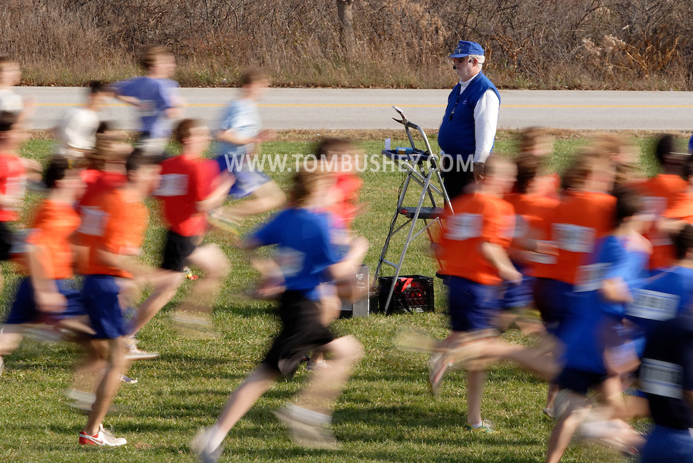 Warwick, N.Y. - Runners streak past the starter at the beginning of a boys' race at the New York State Public High School Athletic Association cross country championships at Sanfordville Elementary School on Nov. 11, 2006.<br />