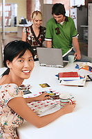 Woman sitting at table with two people using laptop in background.
