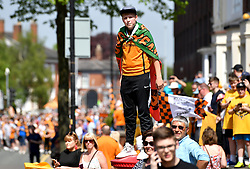 A Wolverhampton Wanderers supporter stands on top of a post box to get a better view during the winner's parade through Wolverhampton.