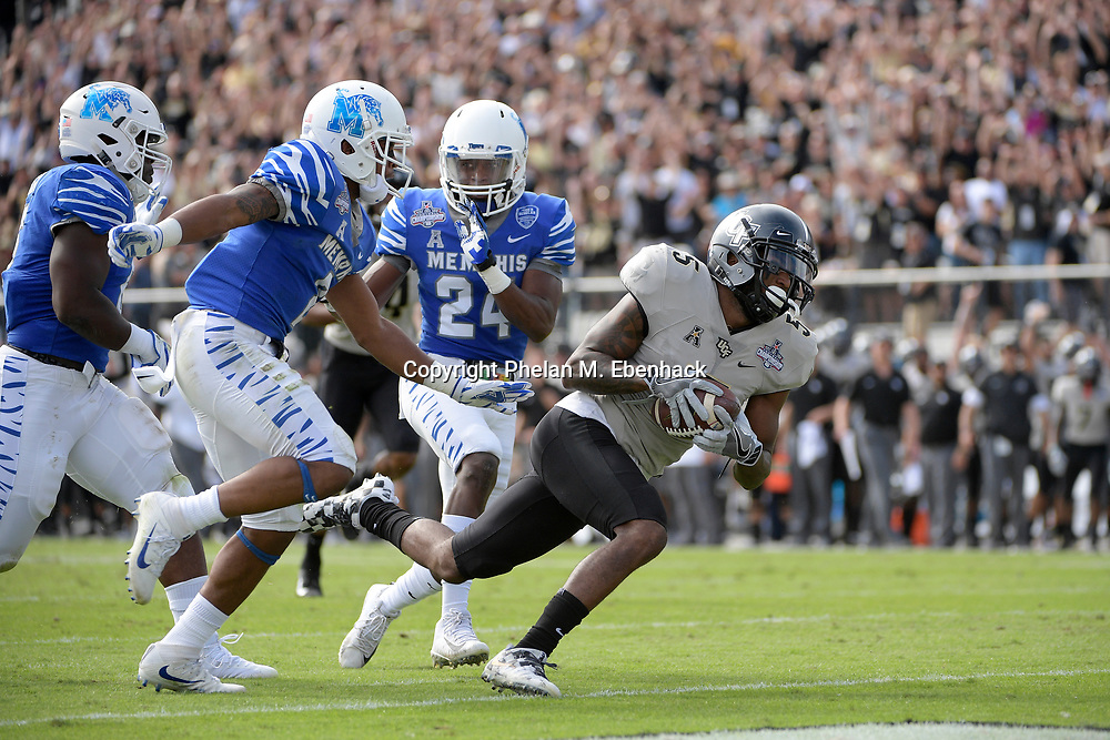 Central Florida wide receiver Dredrick Snelson (5) runs into the end zone for a touchdown in front of Memphis defensive back Terrell Carter (2) and defensive back Tito Windham (24) after catching a pass during the first half of the American Athletic Conference championship NCAA college football game Saturday, Dec. 2, 2017, in Orlando, Fla. (Photo by Phelan M. Ebenhack)