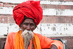Man with big red turban and colorful orange tunic stares into the camera as he sits comfortably on a ghat along the Ganges River, Varanasi, Uttar Pradesh, India