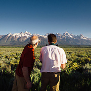 Teten Science Schools tour participants watch a herd of elk forage in the early morning hours. (Greg Peck, Matthew Bart, Sean Baker, Dawson - guide) Tetons in the background.