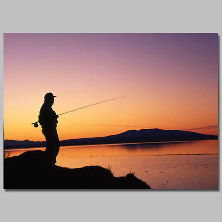Alaska. Man fishing in silouhette with Mt Susitna in background. Turnagain Arm.