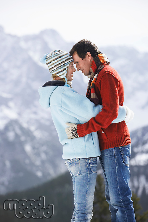 Couple standing face to face in mountains side view