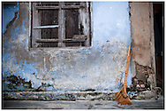 A rudimentary broom is placed along a blue wall in decay. Doc Let, Vietnam, Asia
