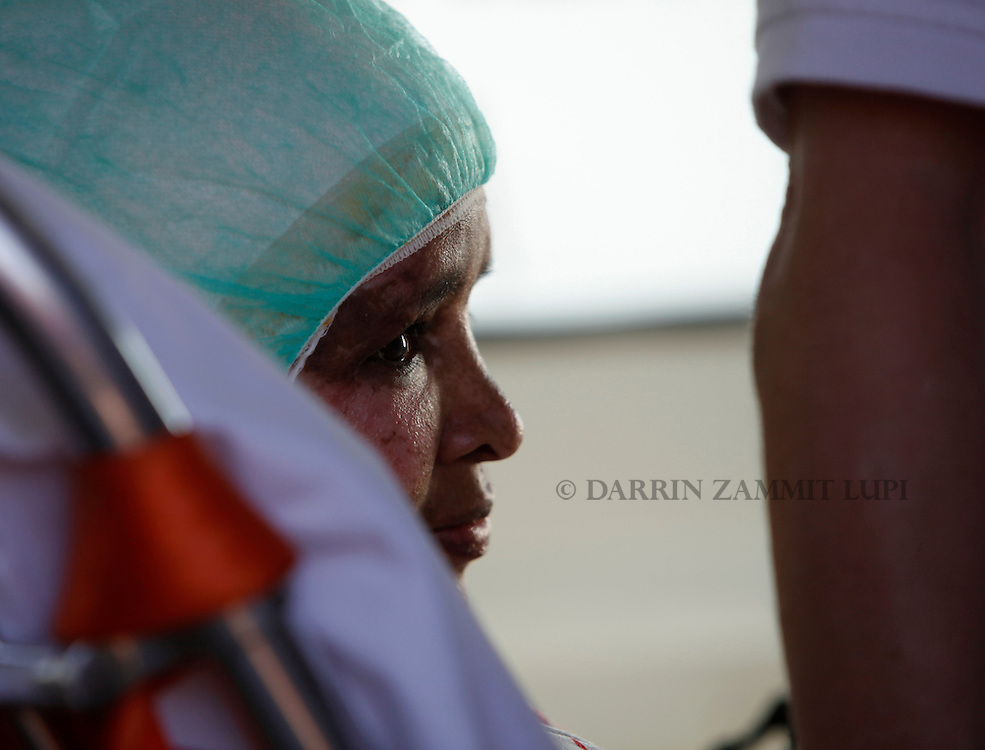 Shwejga Mullah of Ethiopia sits in an ambulance after arriving at Malta International Airport,outside Valletta September 15, 2011. An Ethiopian nanny in the Gaddafi household who suffered horrific burns after she did not stop one of Muammar Gaddafi's grandchildren crying, has arrived in Malta for specialised medical treatment. Shwejga Mullah was recently discovered weak and alone in the home abandoned by Muammar Gaddafi's son Hannibal. She said that  Hannibal Gaddafi's wife Aline threw boiling water over her when she did not stop Hannibal Gaddafi's daughter crying and refused to beat the child. The nanny was brought over in a private plane chartered by the Maltese government.    REUTERS/Darrin Zammit Lupi (MALTA)