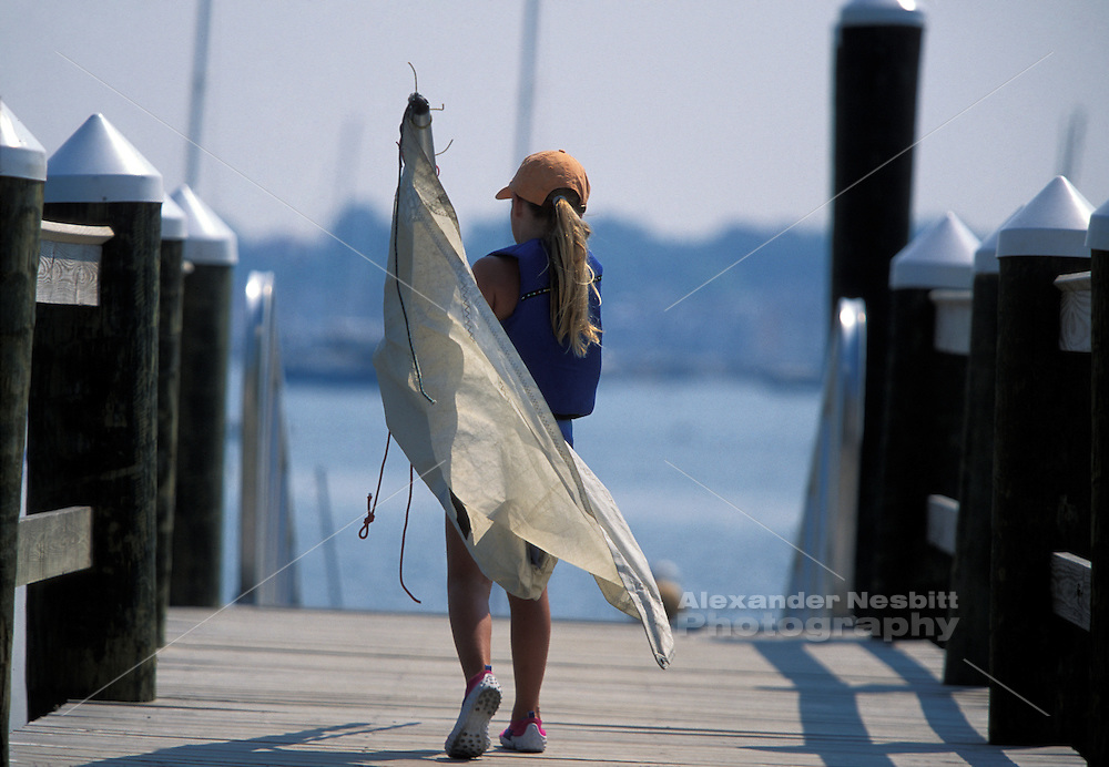 USA, Newport, RI - Girl heads out for Sailing lessons with sail and rig for Optimus dinghy at Sail Newport sailing school.