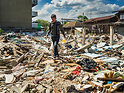27 NOVEMBER 2015 - BANGKOK, THAILAND:  A scavenger walks through the torn down homes in the Wat Kalayanamit neighborhood. Fifty-four homes around Wat Kalayanamit, a historic Buddhist temple on the Chao Phraya River in the Thonburi section of Bangkok, are being razed and the residents evicted to make way for new development at the temple. The abbot of the temple said he was evicting the residents, who have lived on the temple grounds for generations, because their homes are unsafe and because he wants to improve the temple grounds. The evictions are a part of a Bangkok trend, especially along the Chao Phraya River and BTS light rail lines. Low income people are being evicted from their long time homes to make way for urban renewal.             PHOTO BY JACK KURTZ