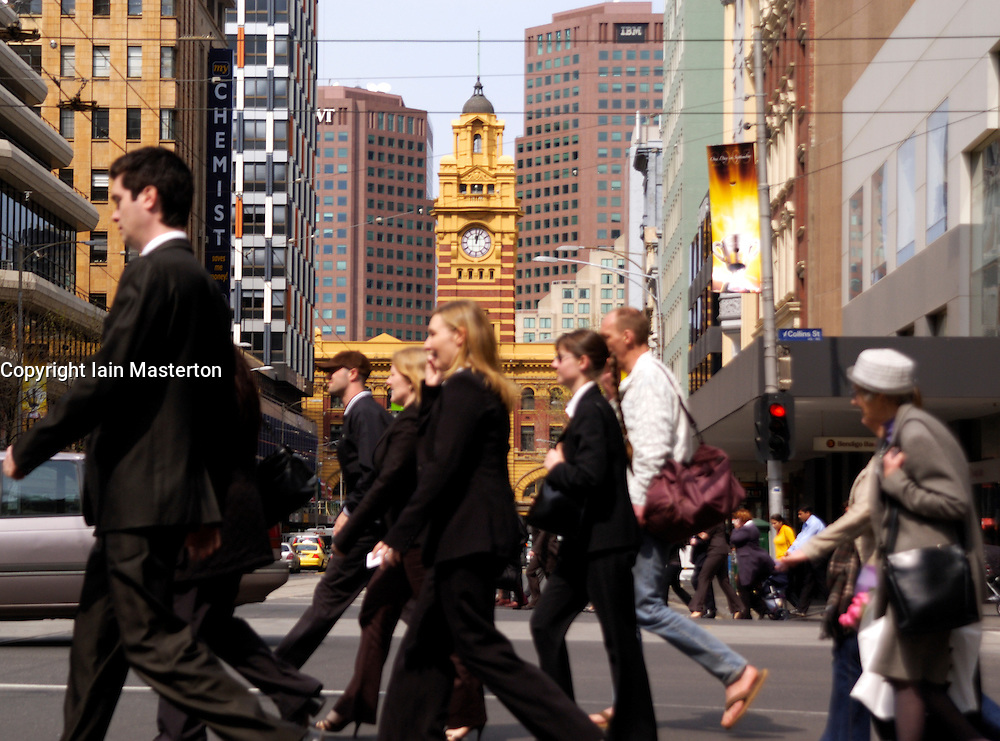 Crowds of office workers cross Collins Street in Melbourne with famous Flinders Street Railway Station to rear