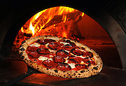 A Spicy Soppressata Pizza is removed from the wood fired oven at Milkflower in Astoria, N.Y.