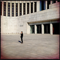 A lone man smokes a cigarette outside of a large building in downtown Pyongyang, North Korea.