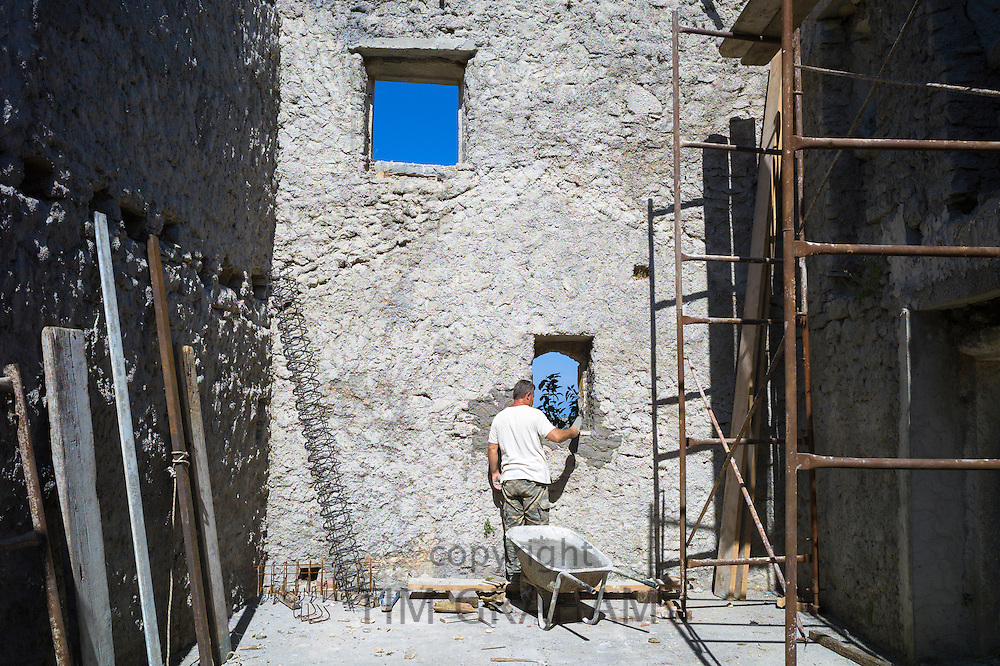 Builder doing masonry building work restoring derelict old stone house in ruins in village of Old Perithia - Palea Perithea, Corfu, Greece