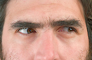 close up of a man's face with his eyes looking to the right