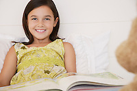 Girl reading story to teddy bears sitting on bed half length