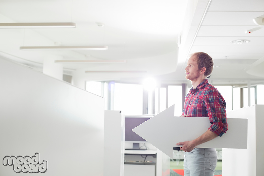 Side view of businessman holding arrow sign in creative office