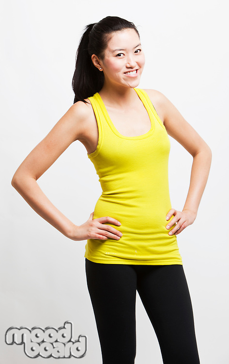 Portrait of young woman smiling with hands on hips against white background